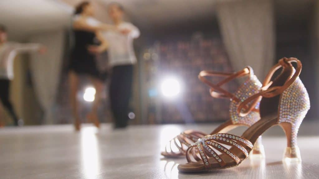 Blurred professional man and woman dancing Latin dance in costumes in the Studio, ballroom shoes in the foreground